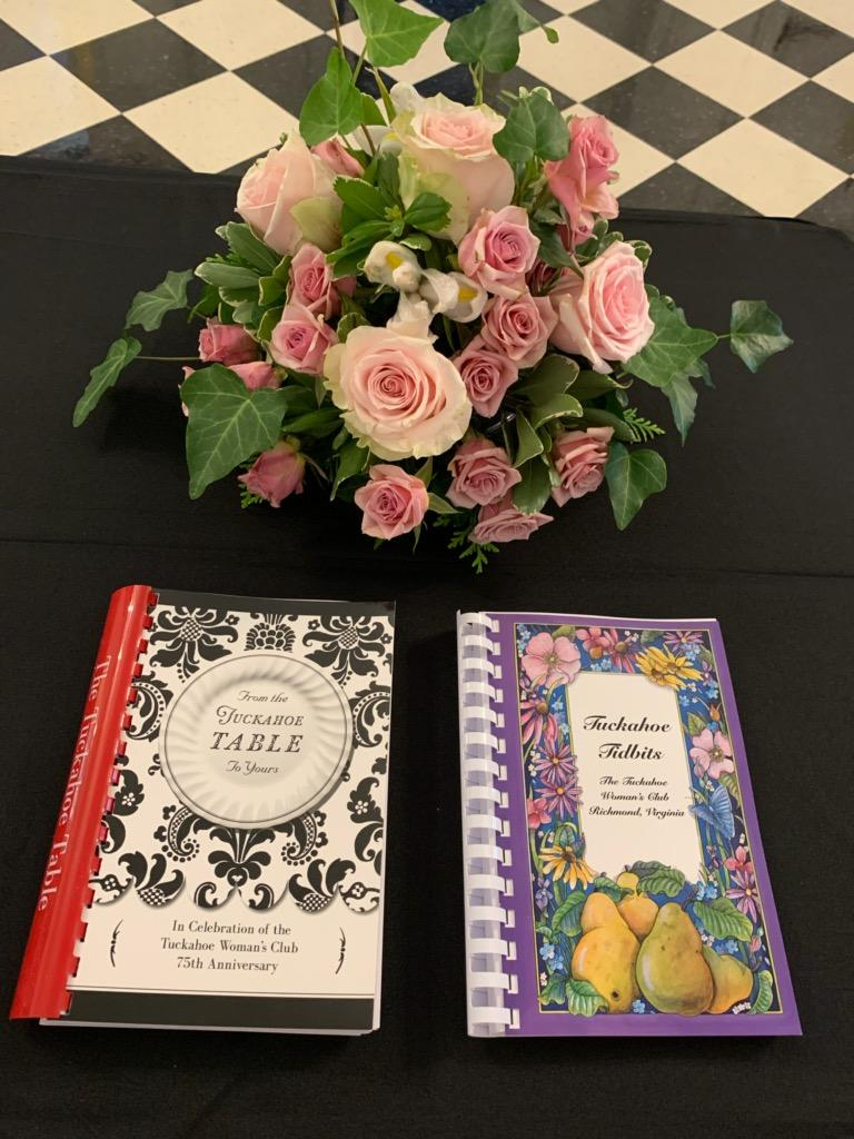 Two cookbooks side by side. One with a black and white cover, one with a purple cover with flowers.