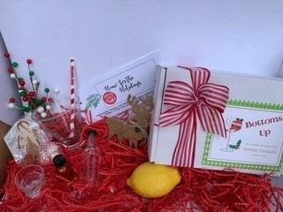red and green cocktail kit with glass, small bottles, lemon, and decorative ornaments.